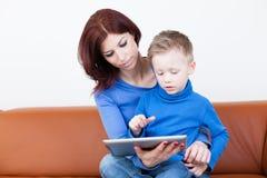 Mãe e filho com PC da tabuleta fotos de stock