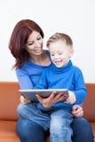 Mãe e filho com PC da tabuleta Fotos de Stock Royalty Free