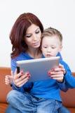 Mãe e filho com PC da tabuleta imagem de stock