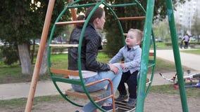 Mãe e filho curioso pequeno que sentam-se junto no balanço no parque filme