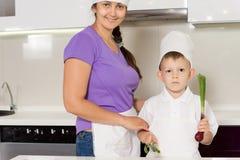 Mãe e filho de sorriso em equipamentos dos cozinheiros chefe Fotografia de Stock Royalty Free