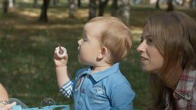 Mãe e filho felizes no retrato exterior de sopro das bolhas de sabão do parque imagem de stock royalty free
