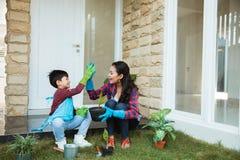 Mãe e filho highfive ao jardinar junto em casa fotografia de stock