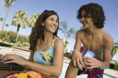 Mãe e filho (13-15) na mãe da piscina que usa o portátil. Imagem de Stock Royalty Free
