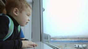 Mãe e filho no aeroporto que gastam a vista do tempo video estoque