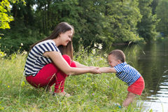 Mãe e filho no parque perto do lago Imagens de Stock Royalty Free
