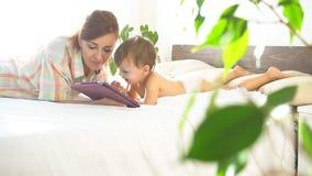 Mãe e filho novo a encontrar-se na cama e para usar o Internet na tabuleta vídeos de arquivo