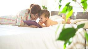 Mãe e filho novo a encontrar-se na cama e para usar o Internet na tabuleta video estoque