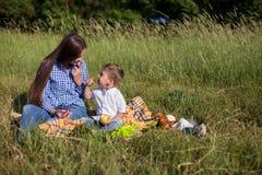 Mãe e filho novo que comem em uma barraca do ar livre do piquenique foto de stock