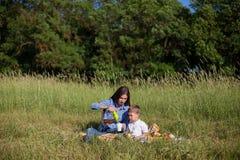 Mãe e filho novo que comem em uma barraca do ar livre do piquenique fotos de stock royalty free