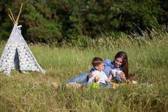 Mãe e filho novo que comem em uma barraca do ar livre do piquenique imagens de stock
