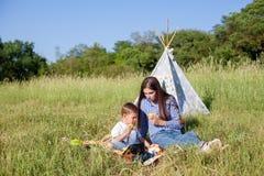 Mãe e filho novo que comem em uma barraca do ar livre do piquenique fotografia de stock royalty free