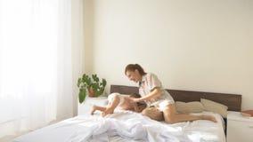 Mãe e filho novo que jogam no quarto na cama video estoque