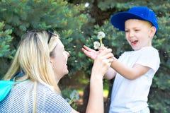 Mãe e filho pequeno que fundem em um dente-de-leão fotografia de stock