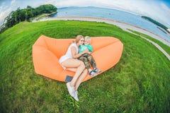 Mãe e filho que descansam em um sofá do ar no parque fotografia de stock royalty free