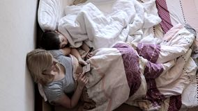 Mãe e filho que encontram-se na cama sob as coberturas e que usam smartphones, procurando o Internet, escrevendo mensagens e jogo video estoque