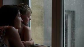 Mãe e filho que esperam alguém para vir olhando para fora a janela durante a chuva