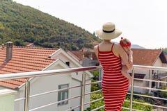 Mãe e filho que estão no balcão em um fundo das montanhas e das casas foto de stock royalty free