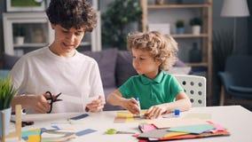 Mãe e filho que fazem as colagens que cortam o papel e que colam com colagem na tabela