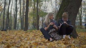 Mãe e filho que fazem trabalhos de casa no parque do outono filme