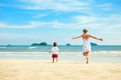 Mãe e filho que funcionam na praia fotos de stock