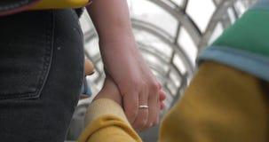 Mãe e filho que guardam as mãos ao montar a escada rolante vídeos de arquivo