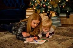 Mãe e filho que jogam no assoalho ao lado de uma árvore de Natal agradavelmente decorada imagens de stock royalty free