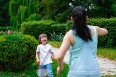 Mãe e filho que jogam o badminton no parque foto de stock