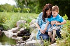 Mãe e filho que jogam perto do lago imagem de stock royalty free