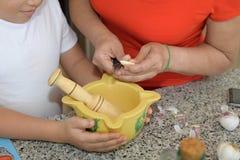Mãe e filho que preparam o almoço Alho do corte imagens de stock royalty free