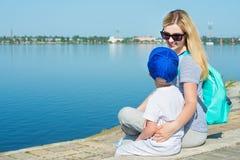 Mãe e filho que sentam-se no passeio e no olhar no rio foto de stock