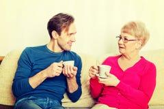Mãe e filho que sentam-se no sofá e chá ou café bebendo imagens de stock royalty free