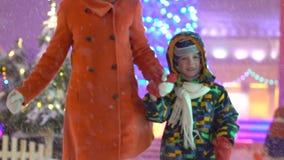 Mãe e filho que têm o divertimento e a corrida que guardam as mãos no fundo da rua do Natal Árvore de Natal Família atrativa video estoque