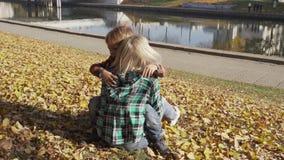 Mãe e filho que têm o divertimento no parque do outono e que encontram-se em uma pilha das folhas amarelas Mamã que abraça o meni video estoque