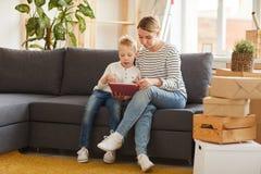 Mãe e filho que usa o app móvel na tabuleta imagens de stock