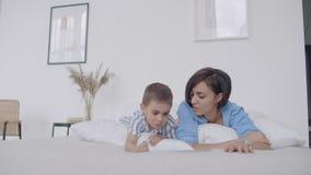 Mãe e filho que usa a tabuleta digital no quarto em casa Ideia dianteira da utilização caucasiano feliz da mãe e do filho digital video estoque