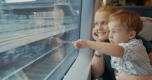 Mãe e filho que viajam em toda a cidade pelo trem video estoque