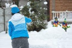 Mãe e filhos que jogam bolas de neve em um dia de inverno gelado Feriados de inverno Divertimento do inverno da família para féri imagem de stock royalty free