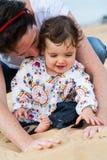 Mãe e infante que jogam na areia Fotografia de Stock