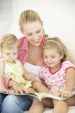 Mãe e livro de leitura das filhas em casa imagem de stock