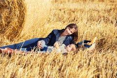 Mãe e menina felizes da criança de dois anos ao lado dos pacotes de feno em um campo Foto de Stock Royalty Free