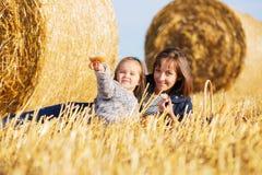 Mãe e menina felizes da criança de dois anos ao lado dos pacotes de feno no campo colhido Fotografia de Stock