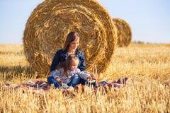 Mãe e menina felizes da criança de dois anos em um campo colhido Imagens de Stock Royalty Free