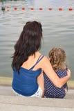 Mãe e menina que contemplam um lago imagem de stock royalty free