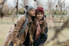 A mãe e o adolescente do doughter estão andando na rua na roupa morna do outono fotografia de stock