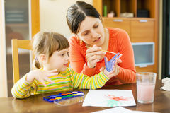 A mãe e o bebê jogam com a aquarela na casa Imagem de Stock