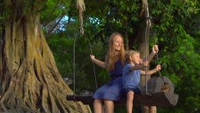 A mãe e o filho balançam nos balanços velhos exóticos que penduram em uma árvore tropical grande em um parque tropical Curso com  filme