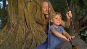 A mãe e o filho balançam nos balanços velhos exóticos que penduram em uma árvore tropical grande em um parque tropical Curso com  video estoque