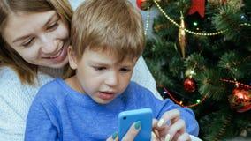 A mãe e o filho com telefone celular estão sentando-se junto perto da árvore de Natal fotografia de stock royalty free