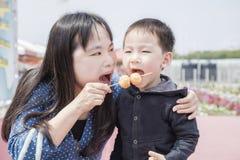 A mãe e o filho comem a bola do polvo Fotografia de Stock